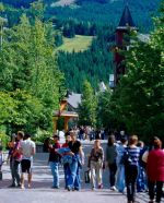 People walking along a pedestrian street in Whistler Village in the summer.